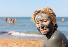 有泥面具的妇女在她的反对海的面孔 图库摄影