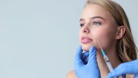 有注射器和女性脸蛋漂亮的医生手 有年轻迷人的妇女扩大嘴唇做法  股票录像