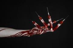 有注射器的在手指,脚趾注射器,手注射器,可怕的血淋淋的手,万圣夜题材,蛇神医生血淋淋的手,黑 免版税库存图片