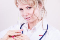 有注射器的白肤金发的医生 免版税图库摄影