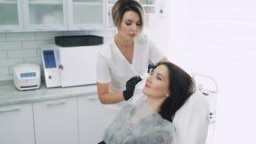 有注射器的美容师做面部秀丽射入给年轻女人,慢动作 股票视频