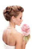 有注视着下来白色backgroun的花束的美丽的新娘 免版税库存图片