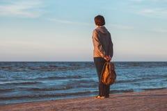 有注视着对海的背包的女孩日落 免版税库存照片