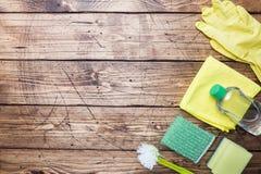 有洗涤剂、刷子和海绵的瓶在木背景 E o r 免版税图库摄影