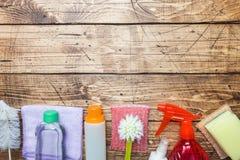 有洗涤剂、刷子和海绵的瓶在木背景 E o r 免版税库存照片