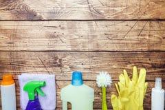 有洗涤剂、刷子和海绵的瓶在木背景 E o r 免版税库存图片