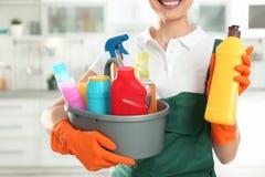有洗涤剂水池和瓶的妇女在厨房里 r 免版税库存图片