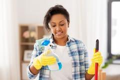 有洗涤剂的非裔美国人的妇女在家 库存照片
