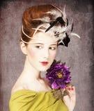 有洛可可式的发型和花的女孩 图库摄影