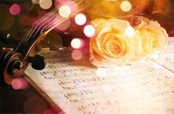 有活页乐谱的小提琴和在黑色的白玫瑰 图库摄影
