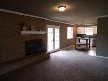 有流动入厨房的壁炉的客厅 库存照片