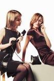 有流动和减速火箭的电话的两名年轻时尚妇女 免版税图库摄影