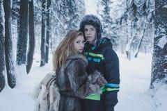 有流动的头发在一件灰色外套和一个人的女孩一个黑夹克和帽子的以冬天森林为背景 图库摄影