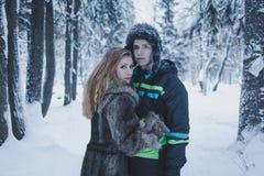 有流动的头发在一件灰色外套和一个人的女孩一个黑夹克和帽子的以冬天森林为背景 免版税库存图片
