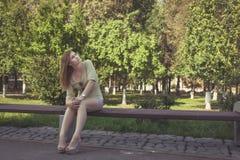 有流动的头发在短的短裤和鞋子的女孩有脚跟的坐长凳 库存照片