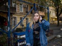 有流动的头发的可爱的女孩在以一个老大厦为背景的一件牛仔布夹克 库存照片