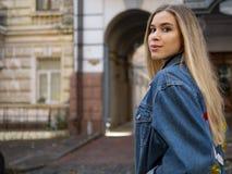 有流动的头发的可爱的女孩在以一个老大厦为背景的一件牛仔布夹克 免版税库存照片