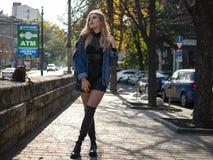 有流动的头发的可爱的金发碧眼的女人在站立在充分的成长的街道上的皮靴 图库摄影