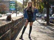 有流动的头发的可爱的金发碧眼的女人在站立在充分的成长的街道上的皮靴 免版税库存照片