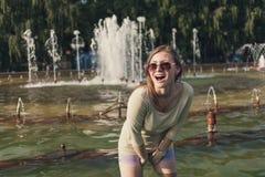 有流动的头发的女孩在短的短裤和太阳镜在喷泉站立 免版税库存照片