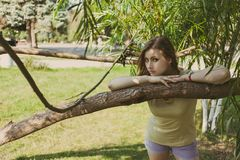 有流动的头发的女孩在短的短裤在绿叶背景的一棵树附近站立  免版税库存照片