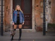有流动的头发的白肤金发的式样女孩在牛仔布夹克站立以与葡萄酒门的一个老大厦为背景 免版税库存图片