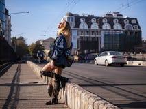 有流动的头发的美丽的时髦的少年女孩在城市桥梁的充分的成长 图库摄影
