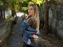 有流动的头发的美丽的金发碧眼的女人在牛仔布夹克在一个石楼梯的背景的街道上站立 免版税库存照片