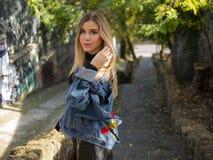 有流动的头发的美丽的金发碧眼的女人在牛仔布夹克在一个石楼梯的背景的街道上站立 库存照片