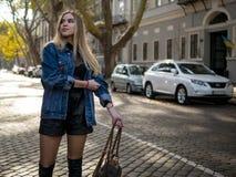 有流动的头发的逗人喜爱的女孩在站立在有停放的汽车的街道上的牛仔布夹克 库存照片