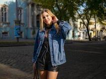 有流动的头发的逗人喜爱的金发碧眼的女人在牛仔布夹克是站立和微笑户外 库存照片
