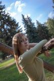 有流动的头发立场的女孩在冷杉木背景的一棵树附近  图库摄影