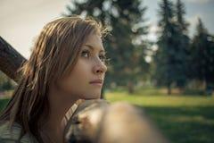 有流动的头发立场的女孩在冷杉木背景的一棵树附近  库存图片