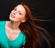 有流动的红色头发的女孩在黑背景 免版税库存图片