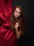 有流动的红色头发的女孩在黑背景 免版税库存照片