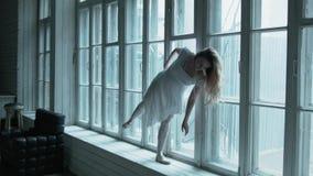 有流动的头发的一个美丽的金发碧眼的女人在窗台站立并且举她的在一个优美的舞蹈的腿 一个年轻人 股票视频