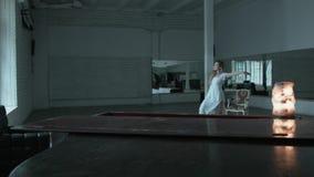 有流动的头发的一个美丽的金发碧眼的女人跳舞在一件白色礼服的一个缓慢的舞蹈 一个少妇在一个白色大厅里跳舞与 影视素材
