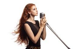 有流动的头发的美丽的女孩唱歌入减速火箭的话筒的 免版税库存图片