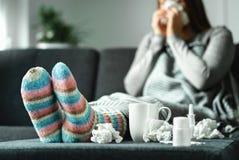 有流感、寒冷、热病和咳嗽的病的妇女在家坐长沙发 不适的人吹的鼻子和打喷嚏与组织 免版税库存图片