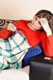 有流感和采取她的温度的少妇 免版税库存图片