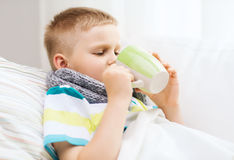 有流感的不适的男孩在家 免版税库存图片