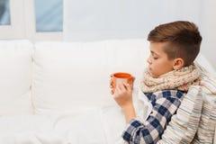 有流感的不适的男孩在围巾饮用的茶在家 库存图片