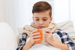 有流感的不适的男孩在围巾饮用的茶在家 免版税库存照片