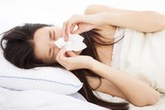 有流感的妇女和放置在床上 库存照片