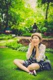 有流行的服装的逗人喜爱的年轻亚裔泰国女孩坐 免版税库存图片
