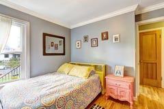 有浅兰的墙壁的简单的卧室 免版税库存照片