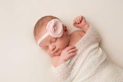 有浅粉红色的花头饰带的新出生的女婴 免版税库存照片