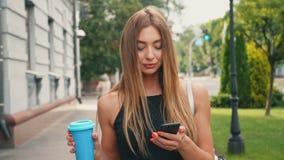 有浅褐色的头发步行的可爱的年轻女人在市中心下,检查她的智能手机和饮料咖啡 股票录像
