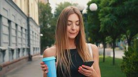 有浅褐色的头发步行的可爱的年轻女人在市中心下,检查她的智能手机和饮料咖啡 股票视频