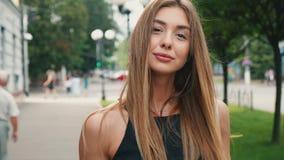 有浅褐色的头发步行的可爱的年轻女人在市中心下,检查她的智能手机和饮料咖啡 影视素材